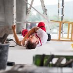 Accident of a male worker at the construction site. An injured man on the floor.